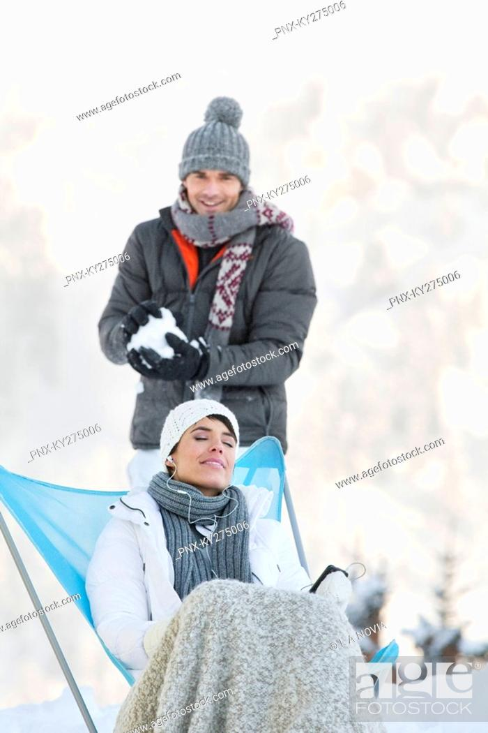 Stock Photo: Young man about to throw snowball at woman resting.