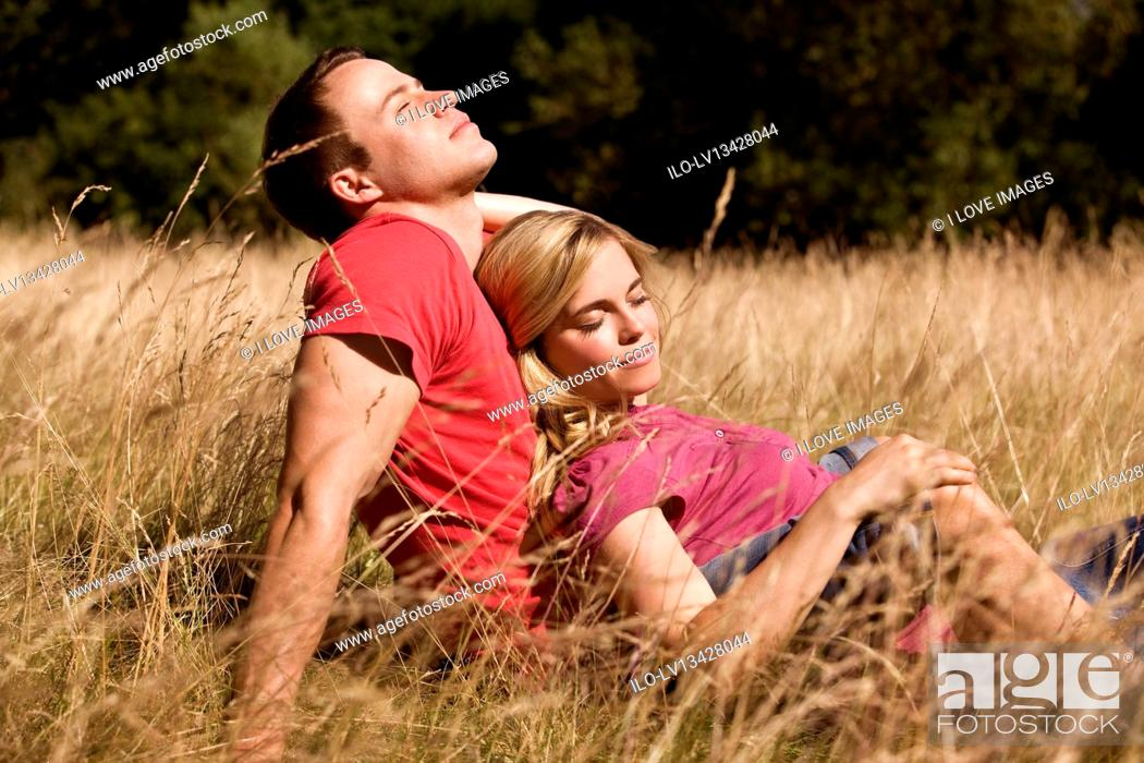 Stock Photo: A young couple sitting in the grass together, enjoying the sun.