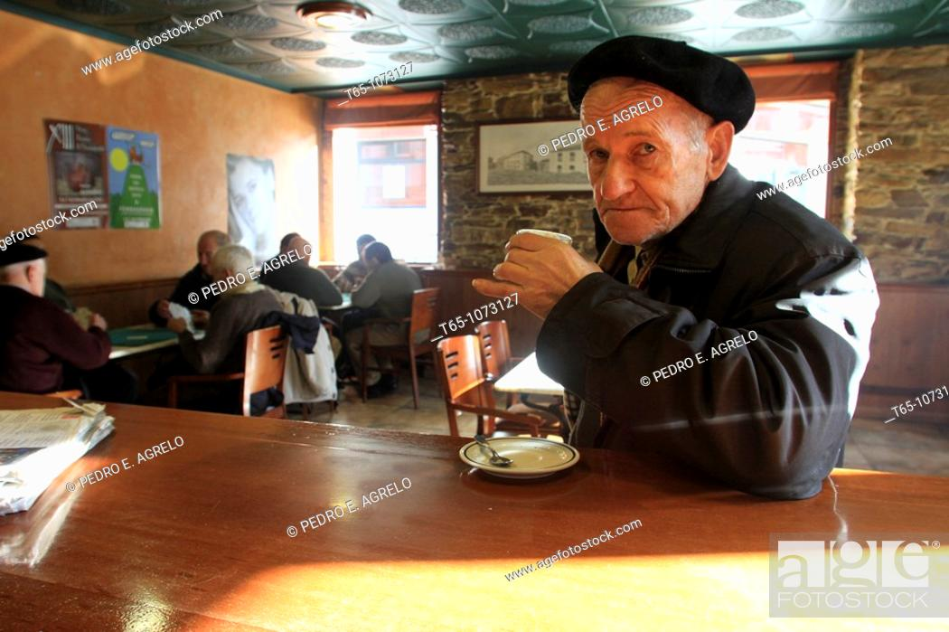 Imagen: Elderly man takes a coffee in a bar while friends play cards in backgroudn. A Fonsagrada (Lugo).