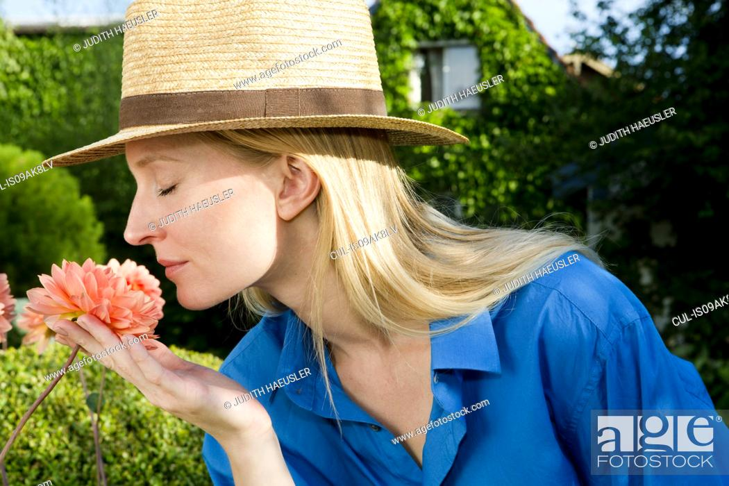 Stock Photo: Close up of mid adult woman smelling garden bloom.