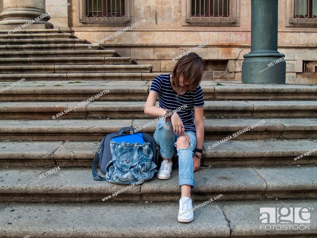 Imagen: A teenage woman gesturing on the stairs of an old building on a university campus.