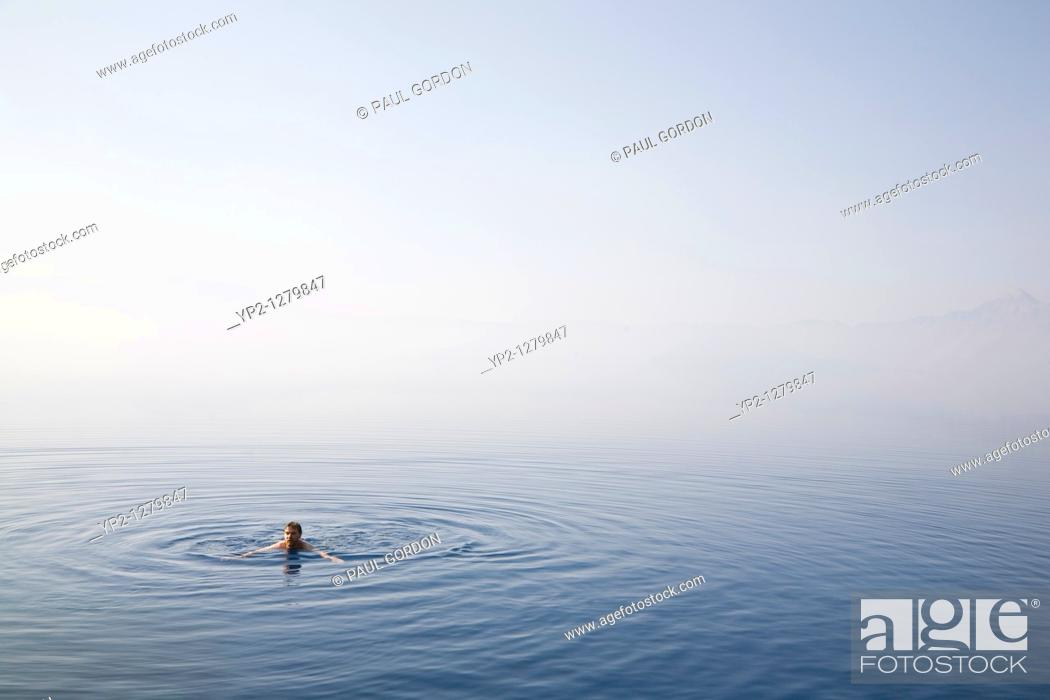 Stock Photo: Man swimming in Cleetwood Cove  Morning mist obscures the rim and horizon line - Crater Lake National Park Oregon.