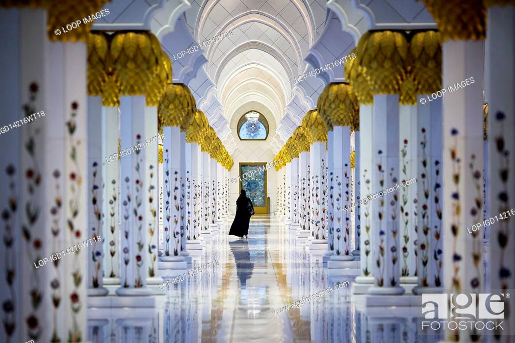 Stock Photo: Woman walking in the cloisters at Sheikh Zayed Grand Mosque.