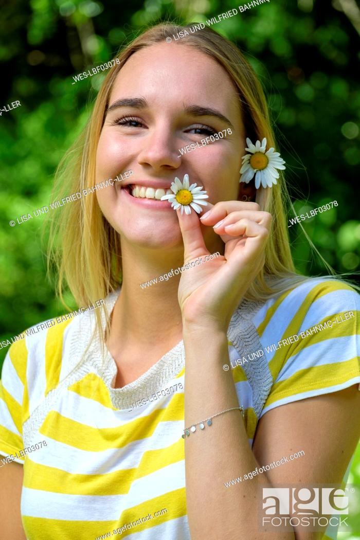 Stock Photo: Close-up of smiling beautiful woman holding oxeye daisies in park.