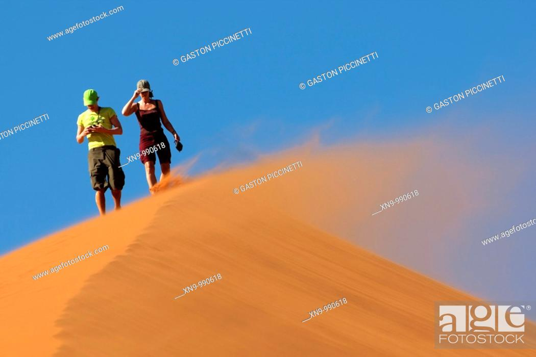 Stock Photo: People climbing the sand dune in a windy day, Namib-Naukluft National Park, Namib desert, Namibia.