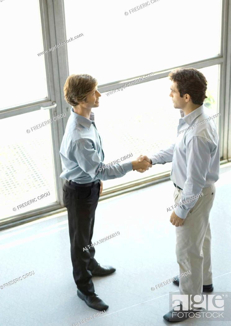 Stock Photo: Two businessmen shaking hands, full length.