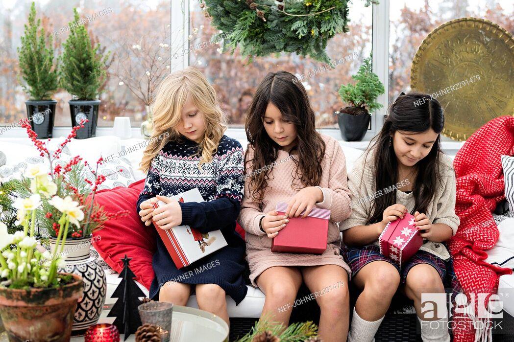 Stock Photo: Three girls opening presents.
