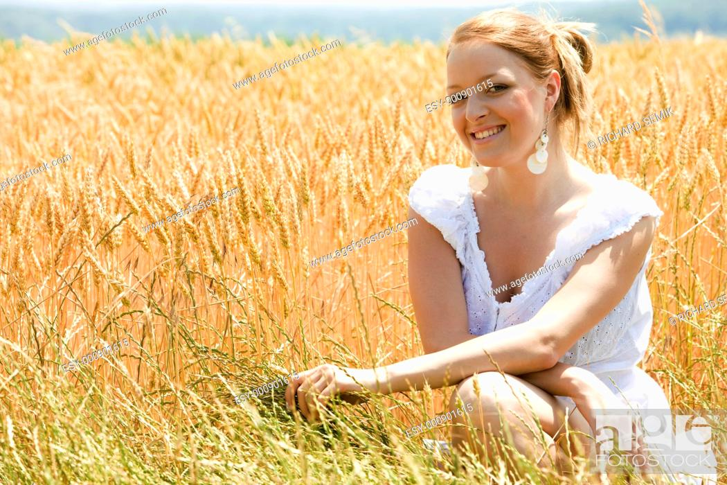 Stock Photo: portrait of woman sitting in grain field.