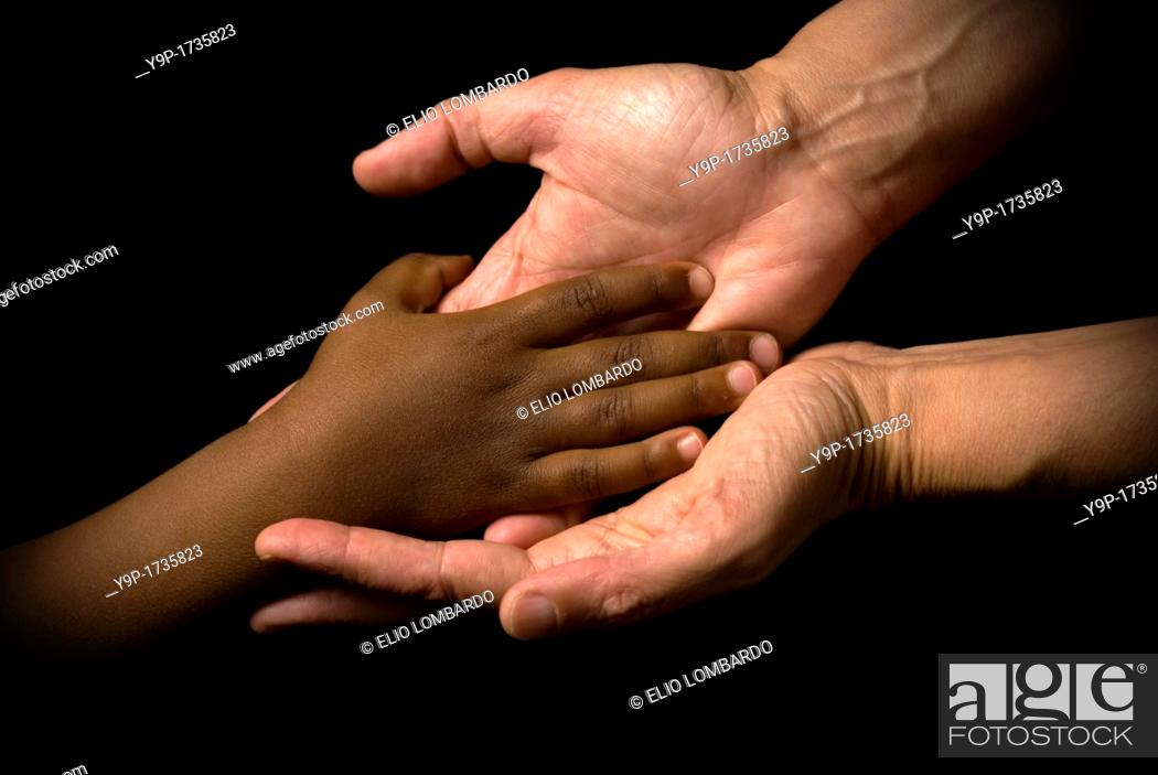 Stock Photo: White woman's hands receive the black child's hand.