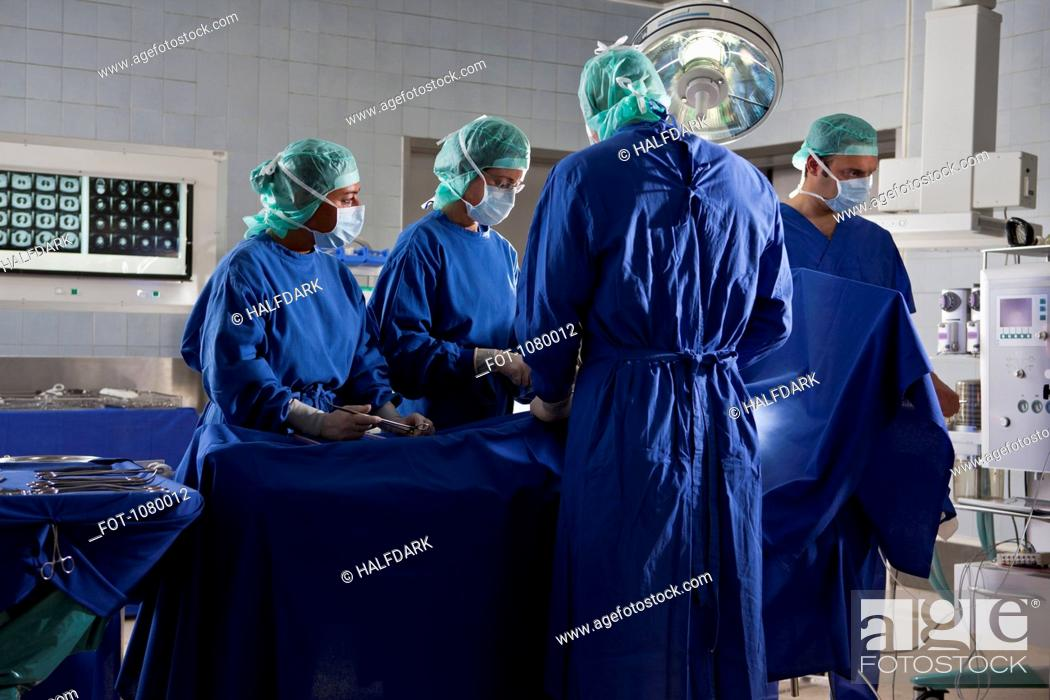 Stock Photo: A surgery team operating on a patient in an operating room.