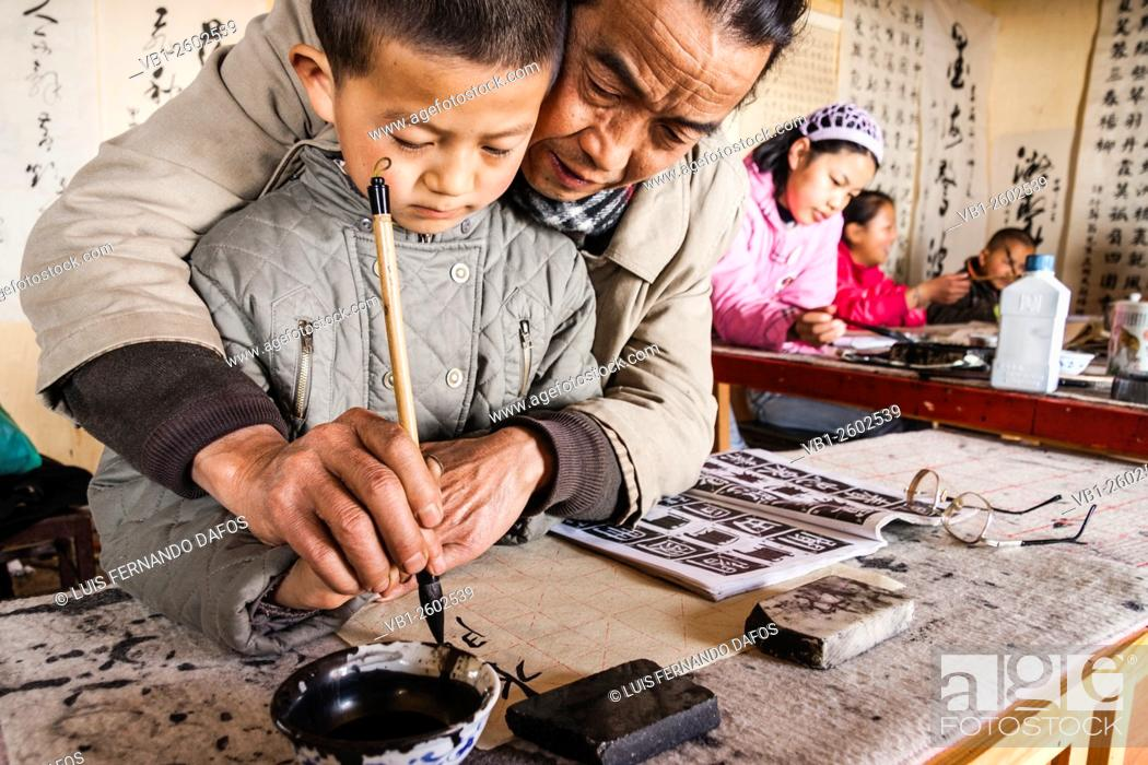 Stock Photo: Teacher and pupil at traditional calligraphy school. Lijiang, China.