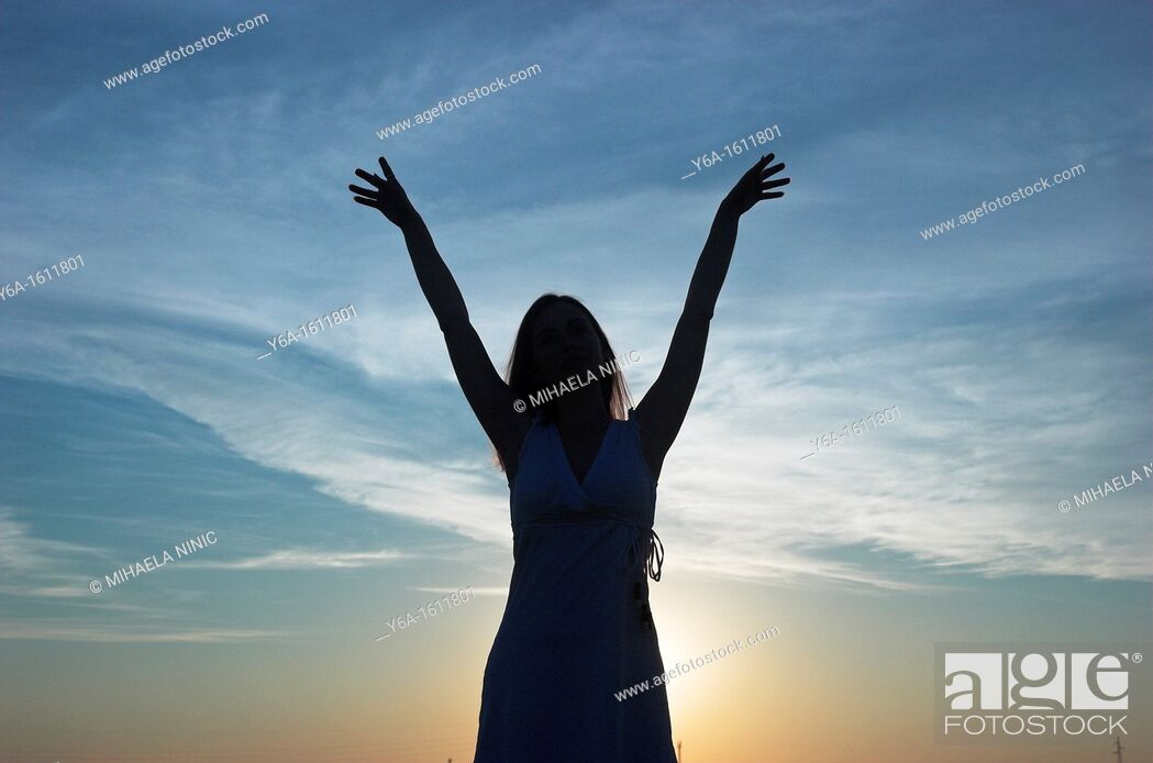 Stock Photo: Silhouette of a young woman at dusk arms raised.