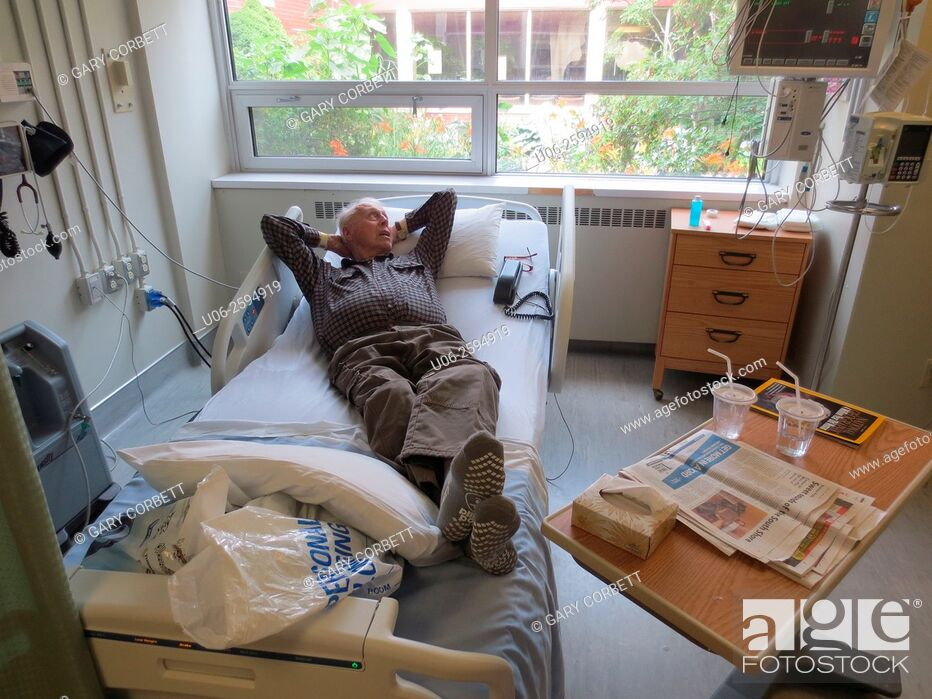 Stock Photo: A senior man lying on a hospital bed, well and ready to leave.