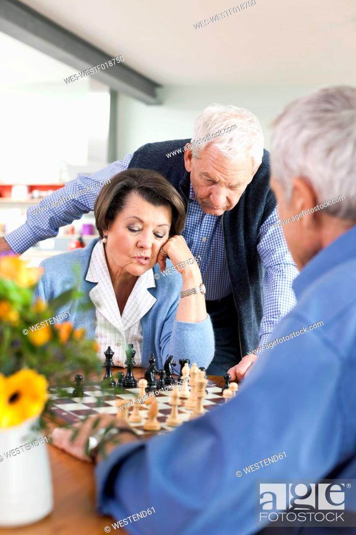 Stock Photo: Germany, Leipzig, Senior men and woman playing chess.