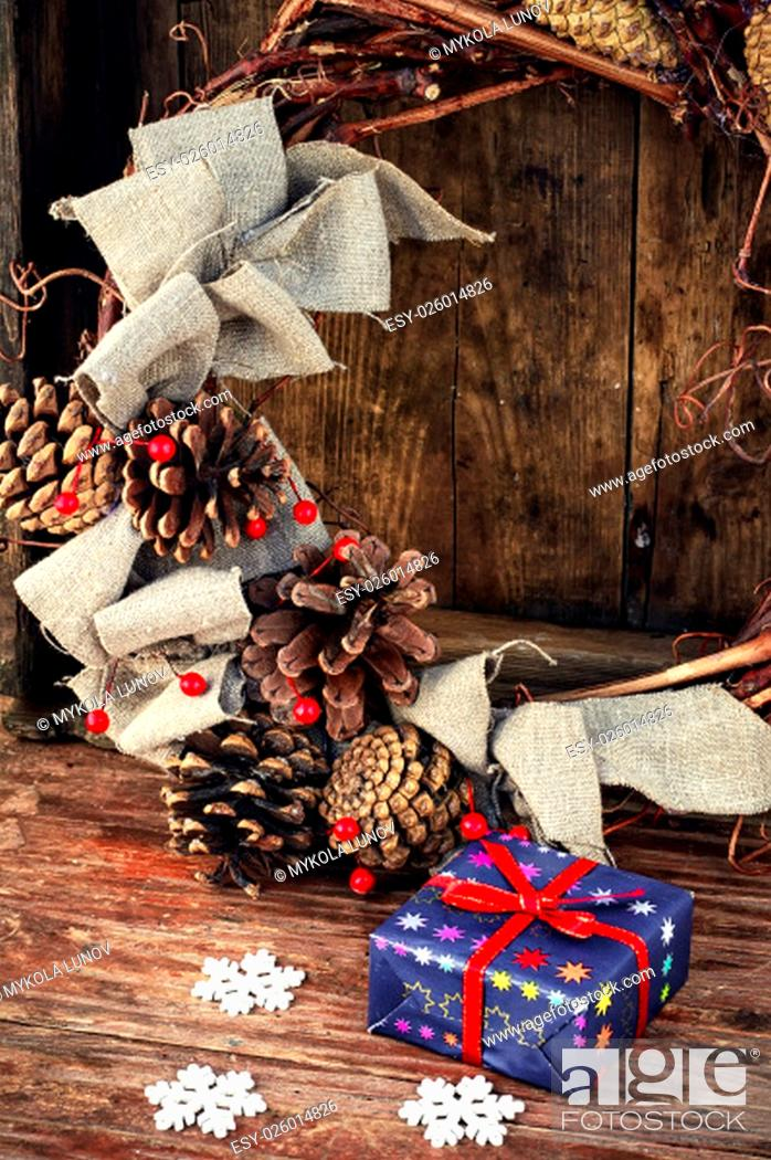 Stock Photo: gift box on the background of a wicker wreath decorated for Christmas with pine cones and berries.