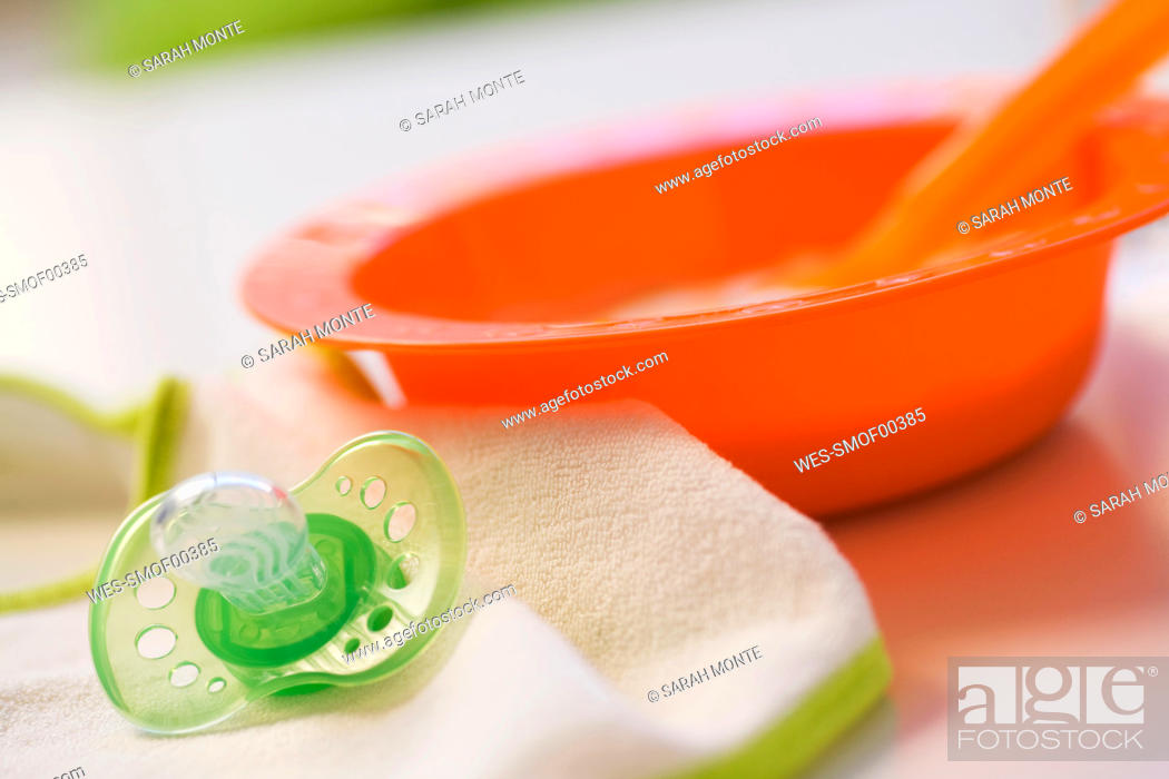 Stock Photo: Baby food in bowl with pacifier.