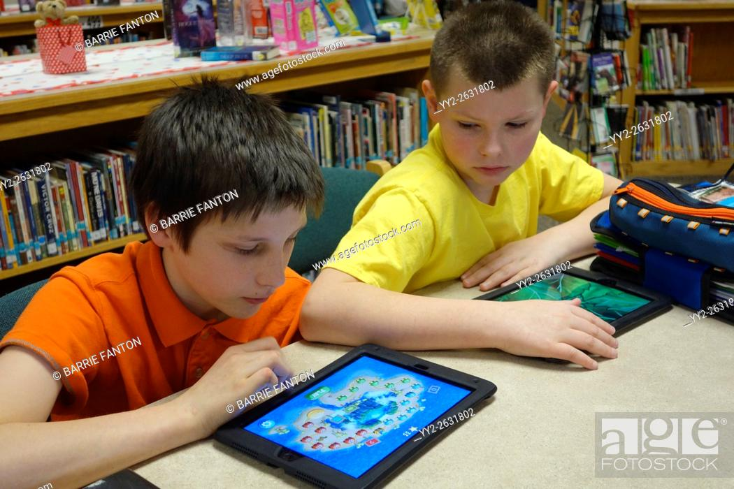 Stock Photo: Preteen Boys Using iPad to Learn Coding for School Assignment, Wellsville, New York, USA.