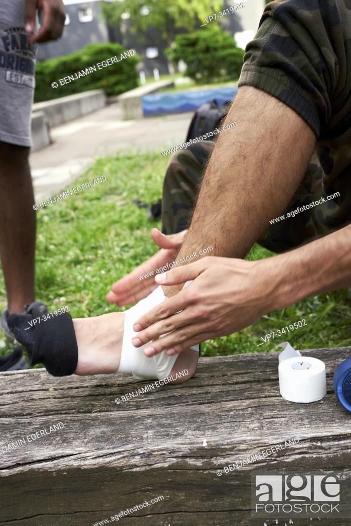 Stock Photo: Close-up of man putting on a bandage on his ankle before performing acrobatic exercise.