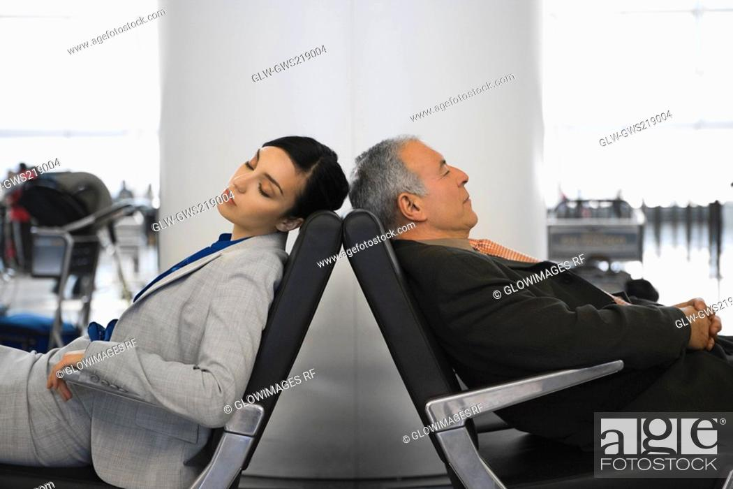 Stock Photo: Side profile of a businessman and a businesswoman sleeping on chairs at an airport.