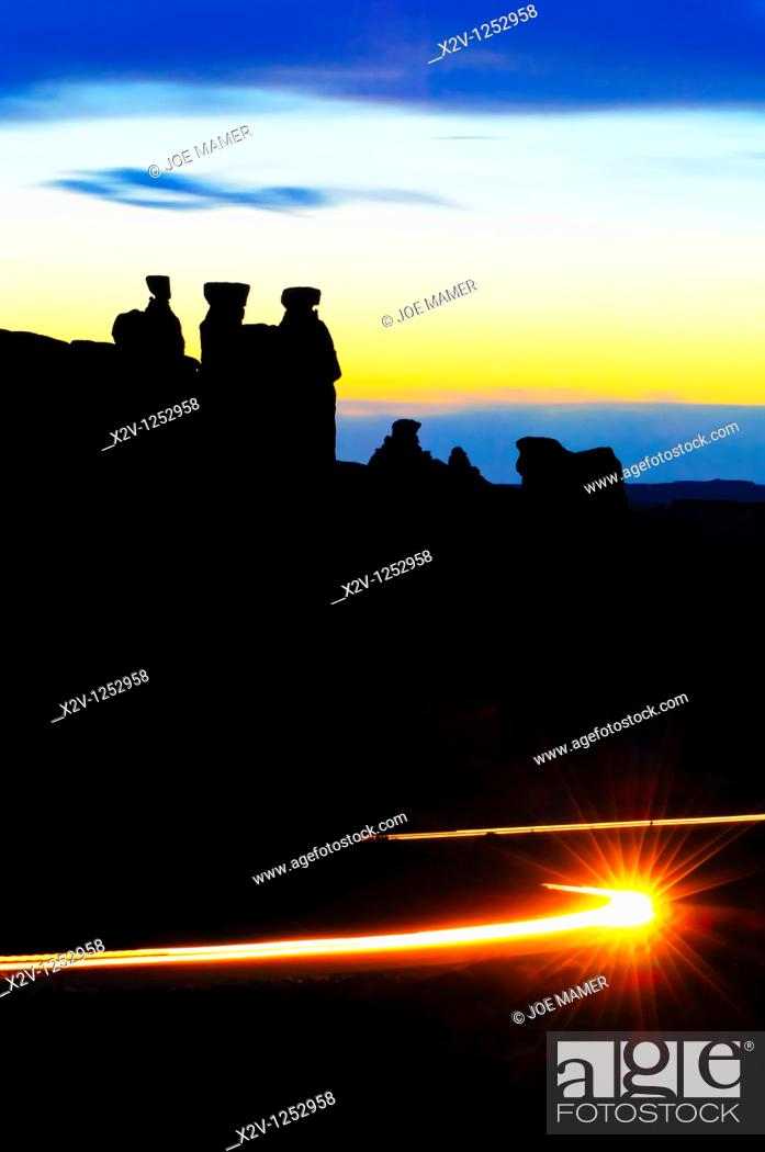 Stock Photo: Three gossips at Arches National Park silhouetted against the sunset  Car lights in the foreground trace the path of the road.