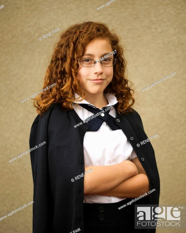 Stock Photo: School age mixed race Mexican & caucasian girl with glasses in school uniform.