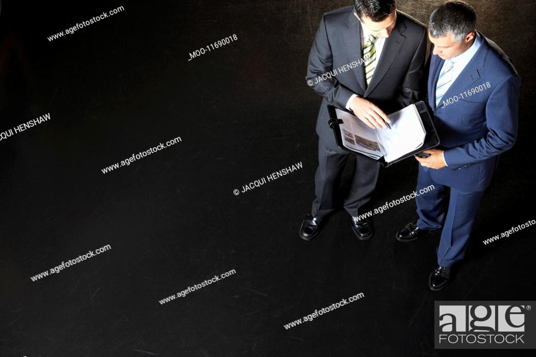 Stock Photo: Elevated view of two businessmen reading documents against dark background.