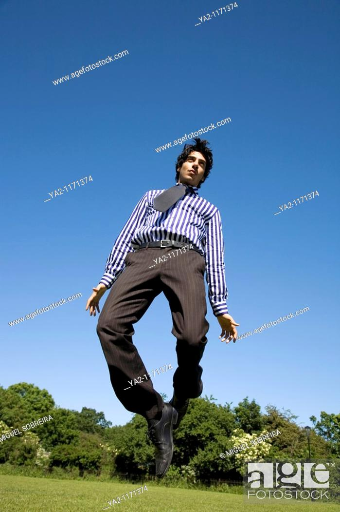 Stock Photo: Man in shirt, tie and trousers jumping in park.