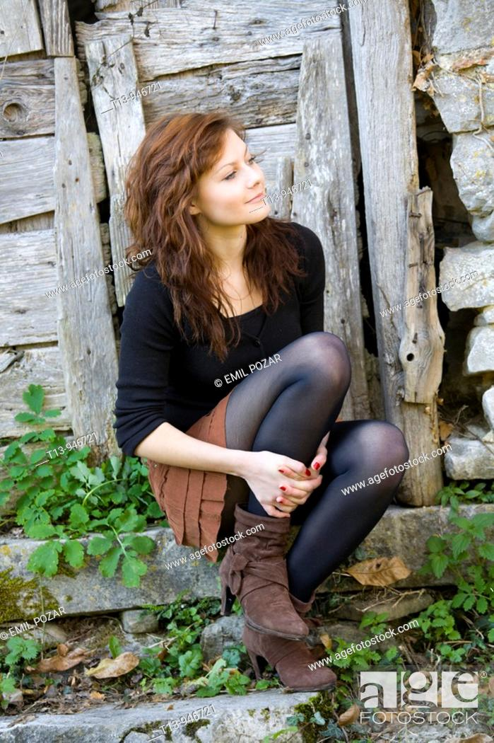 Stock Photo: Pretty young woman is sitting and holding up one leg.