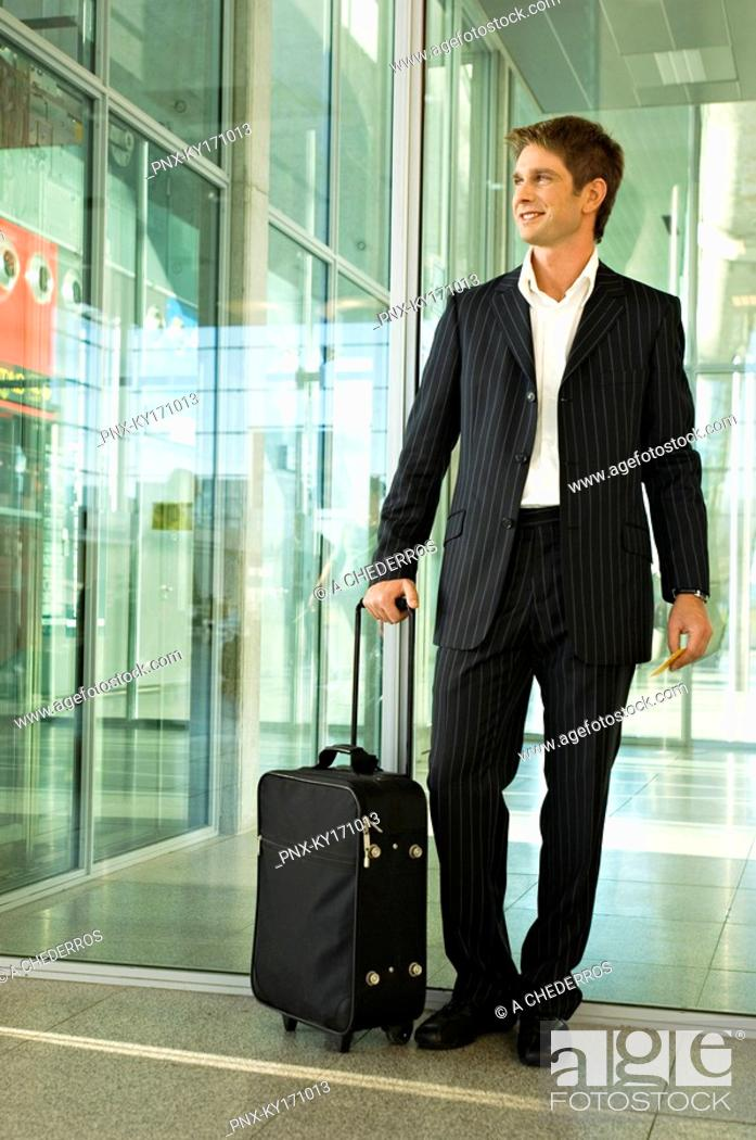 Stock Photo: Businessman standing with his luggage at an airport.