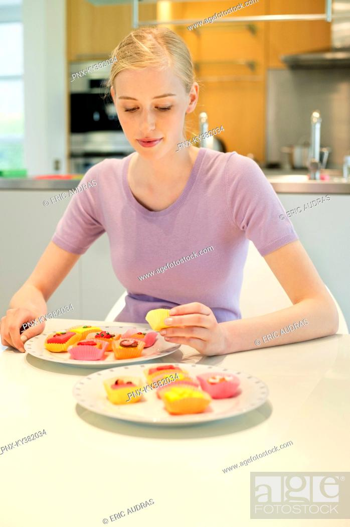 Stock Photo: Woman with cakes at dining table.