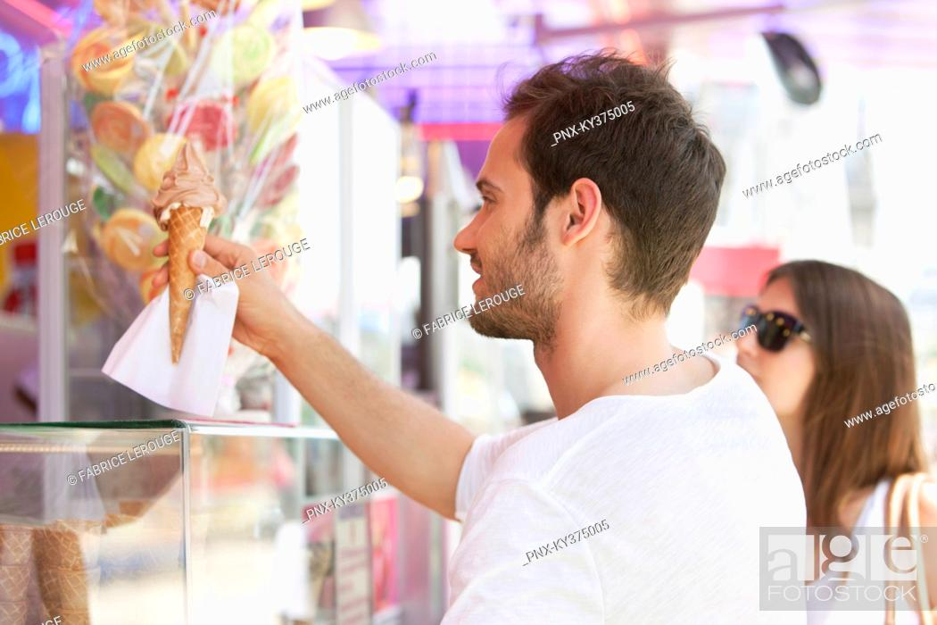 Stock Photo: Man taking ice cream from an ice cream parlor, Paris, Ile-de-France, France.