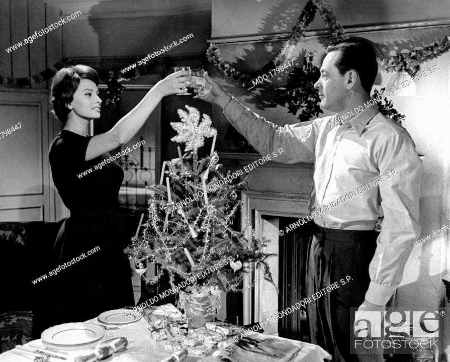 Sophia Loren And William Holden Toasting Near A Christmas Tree In A