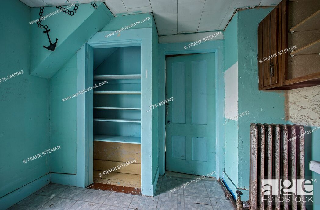 Stock Photo: Empty teal colored room in an abandoned house with only a radiator and empty shelves.