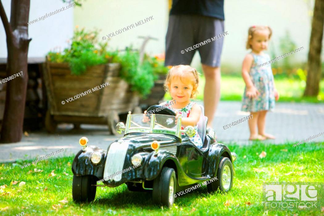 Stock Photo: The little baby girl playing at car against green grass.