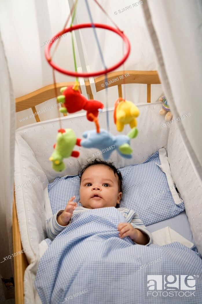 Stock Photo: Two months old boy lying in his cot.