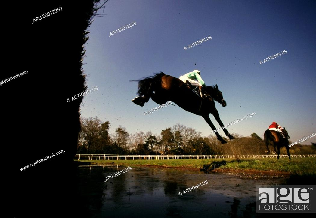 Stock Photo: Below fence view as steeplechasing horses clear water jump fence.