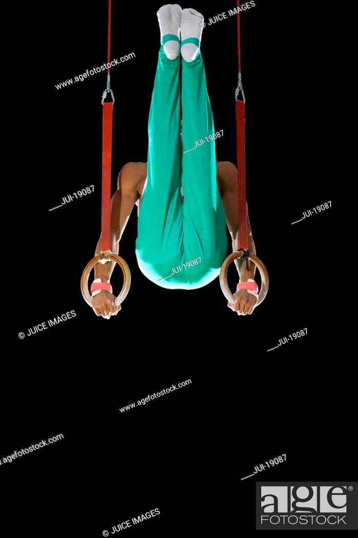 Stock Photo: Male gymnast performing on gymnastic rings, low angle view.