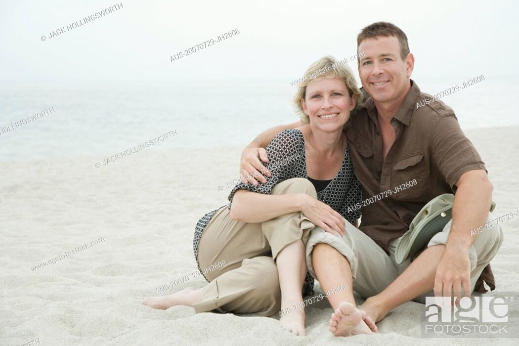 Stock Photo: Portrait of a mature couple sitting on the beach.