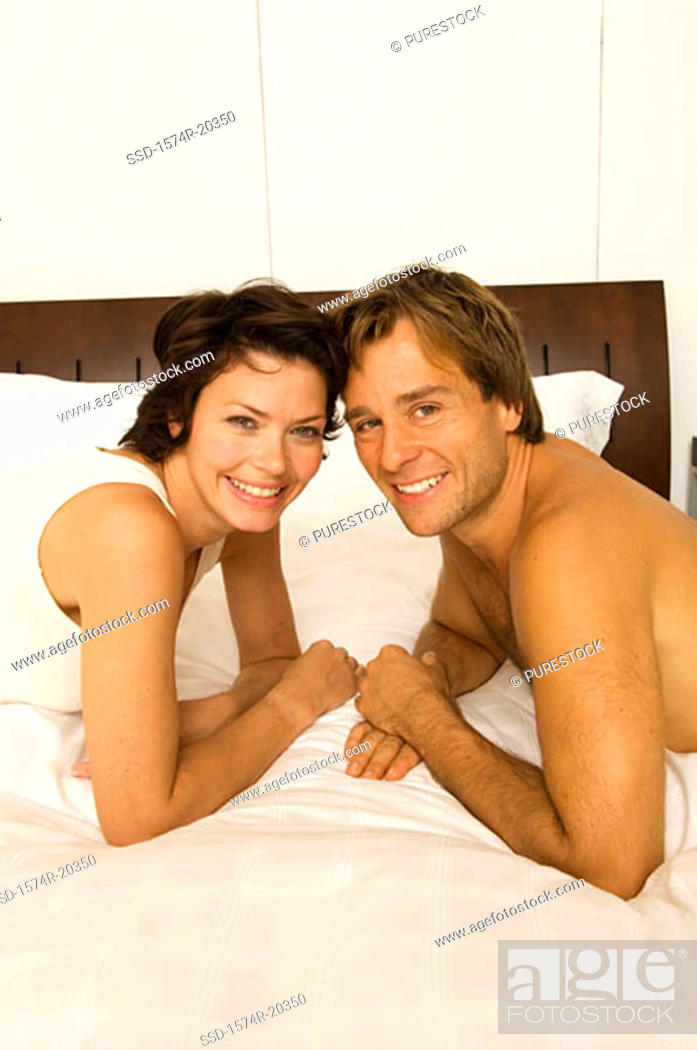 Stock Photo: Portrait of a young couple lying in the bed and smiling.