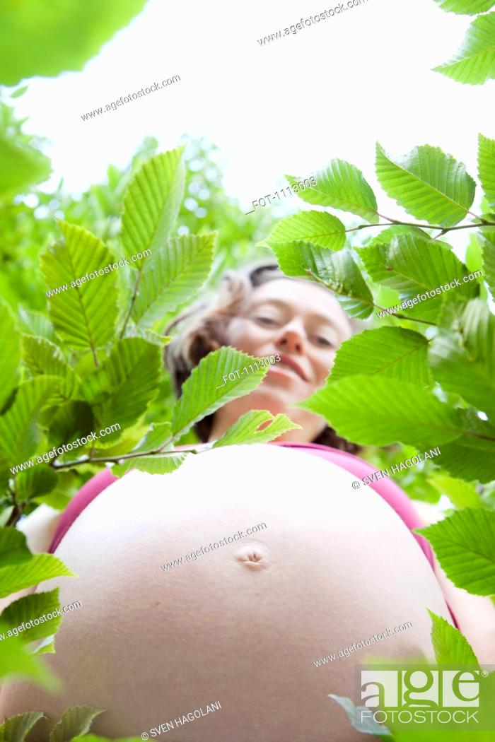 Stock Photo: A smiling pregnant woman's abdomen encircled by leaves.