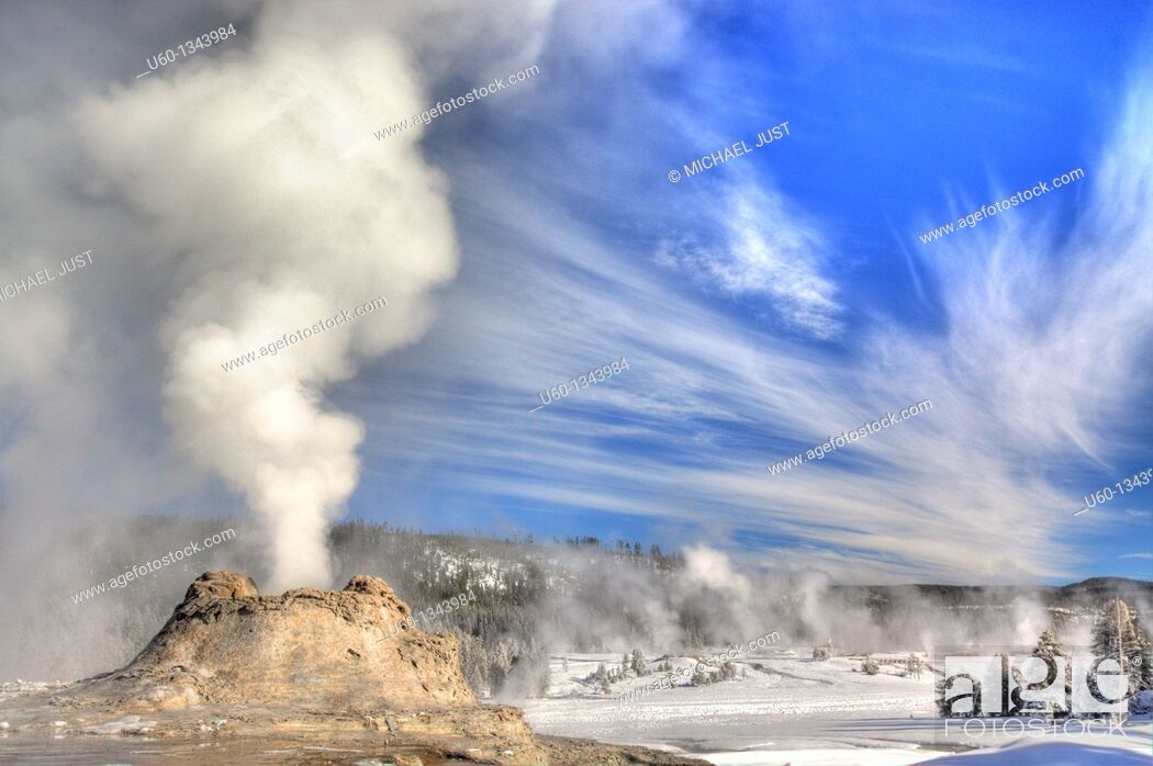 Stock Photo: Castle Geyser erupts under a bright sky at Yellowstone National Park.