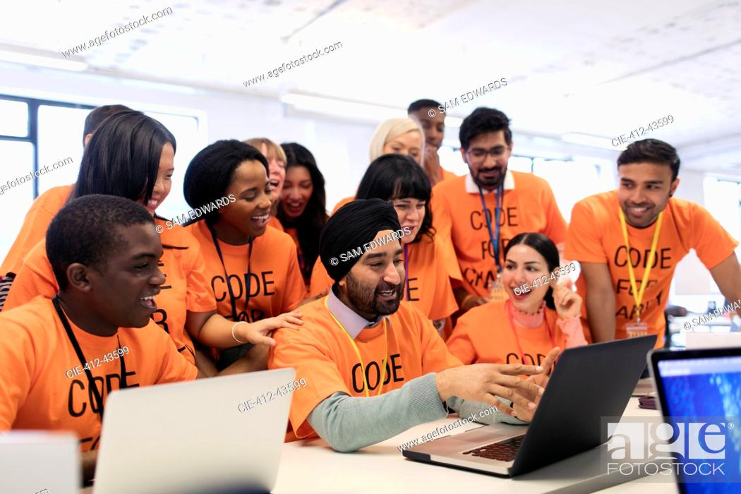 Stock Photo: Happy hackers at laptop coding for charity at hackathon.
