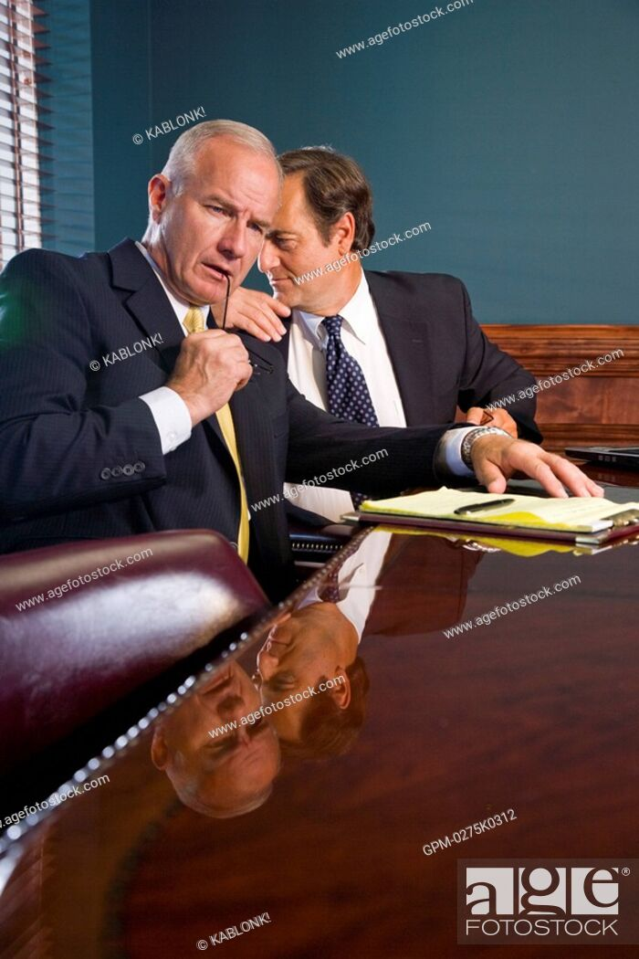 Imagen: Two corporate executives having private conversation in conference room.