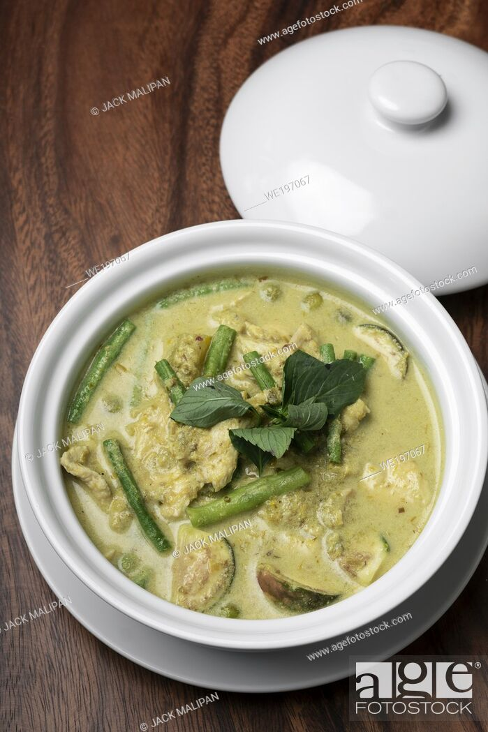 Imagen: thai green curry with chicken and vegetables on wood table.