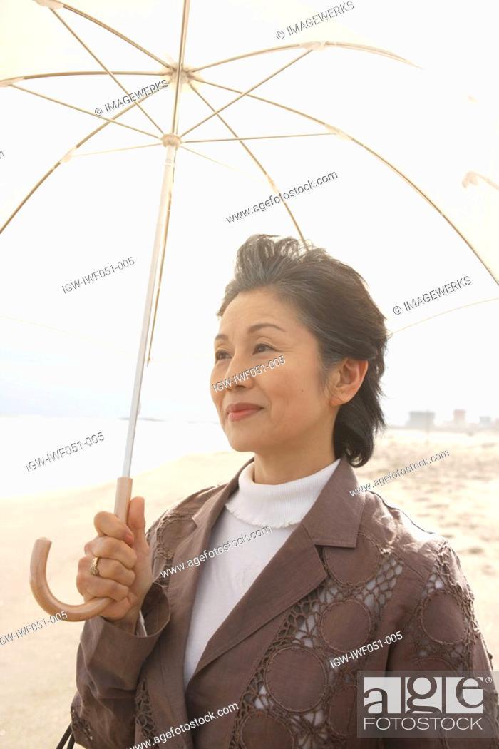 Stock Photo: Senior woman with umbrella at beach.