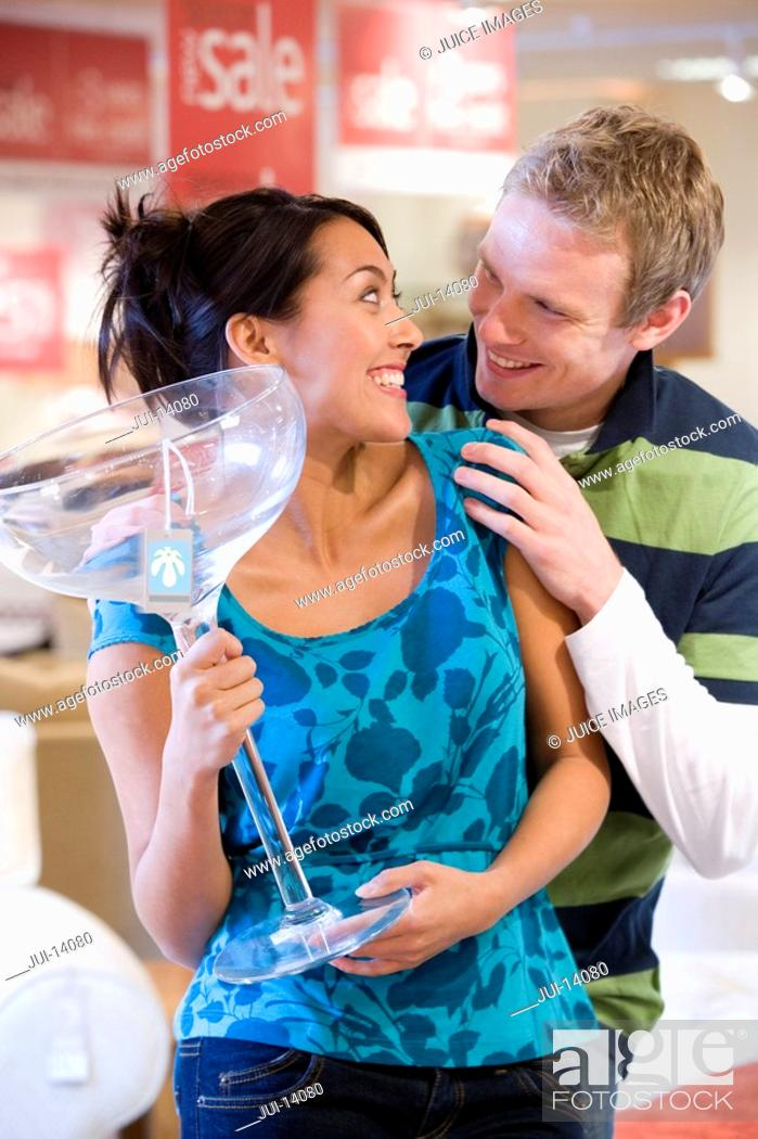 Stock Photo: Young woman with giant cocktail glass in shop, smiling at man.