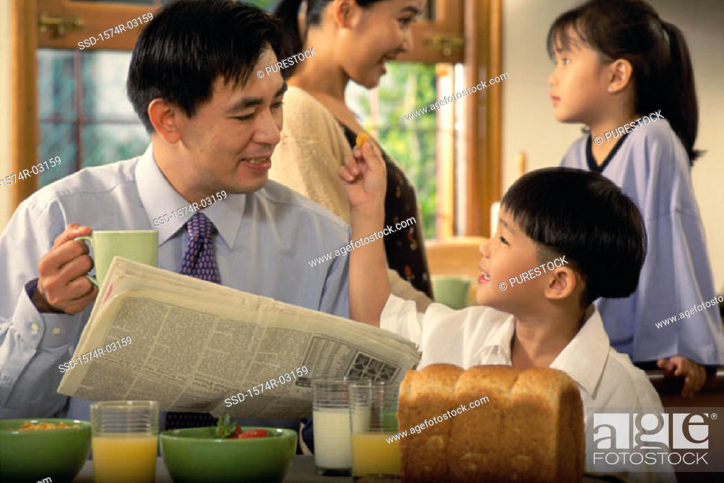 Stock Photo: Father holding a newspaper talking to his son.