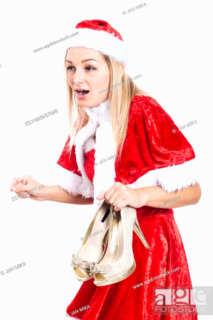 Stock Photo: Shocked woman in Christmas costume holding high heel shoes, isolated on white background.