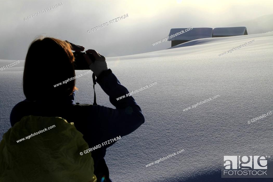 Stock Photo: Hiker takes photograph of snowy log cabins in the distance.