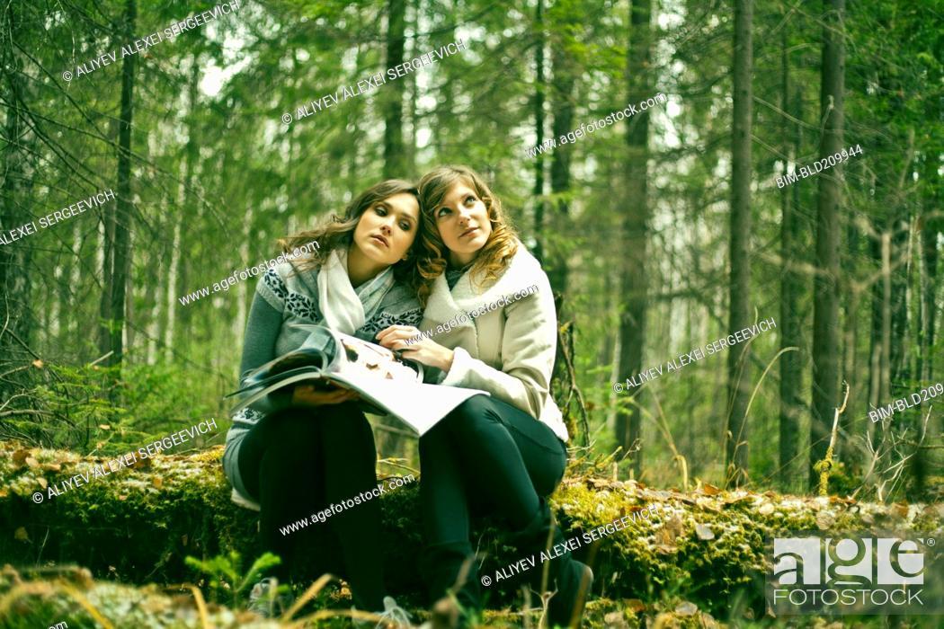 Stock Photo: Caucasian women reading magazine in forest.